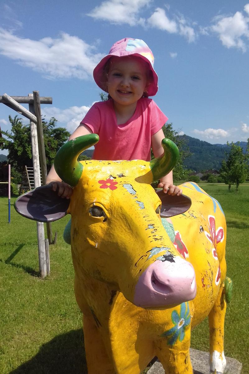 Kind reitet auf einer Kuhfigur